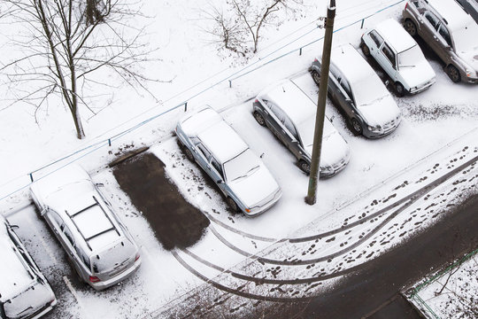 First snow. Cars under snow on a parking after blizzard