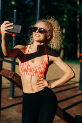 Photo of smiling sports woman wearing sunglasses doing selfie in