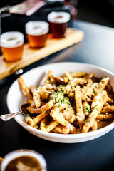 Bowl of poutine with pint glasses