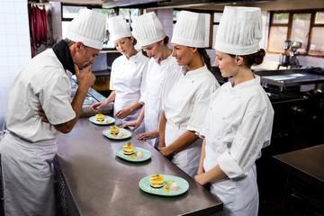 Head chef inspecting dessert plates