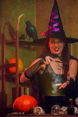 Photo of witch in black hat with magic wand and cauldron