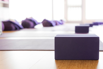 Empty, bright Yoga studio with mats and foam blocks. Wooden floor. Horizontal.