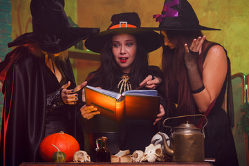 Image of three witches with book in hands