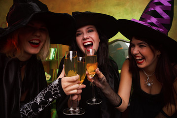 Picture of three happy witches with glass of champagne