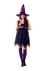 Full-length image of happy witch with wine glass with wine in black dress and hat