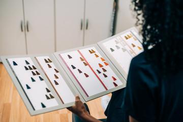 Woman choosing hair color in dye catalog