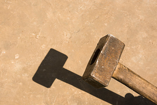 Sledge hammer with shadow on concrete surface