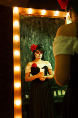 Picture of zombie girl with white face and red flower on her head