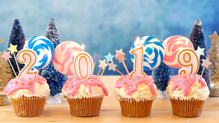 2019 Happy New Year's candy land lollipop drip cupcakes in colorful party table setting.
