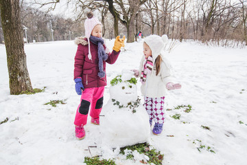 Children Playing With A Snowman In The Park At Winter Day
