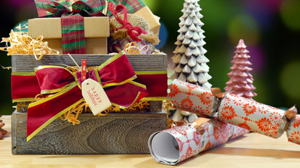 Large English style traditional Christmas hamper with paper wrapped gifts and food against bokeh lights of Christmas Tree.