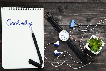Goal setting in notepad with earphones, wrist watch and green plant on wooden table