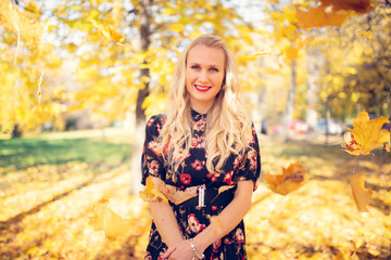 Image of smiling woman in dress on blurred background of autumn park