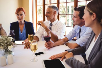 Business people interacting with each other on table