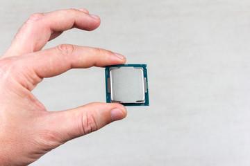 man holding fingers mock up desktop processor 8th gen on grey background closeup top view