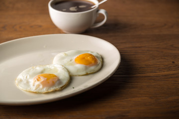 Aluminium Prints Egg Fried Eggs on white plate and cup of black Coffee for Breakfast on wooden background