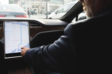 Businessman using navigator map while driving a car