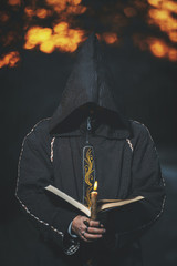 Cosplay black mage. A man dressed as a monk. A man in a black robe with a copier. Halloween costume. A man with a book and a candle. Homemade costume of the evil sorcerer