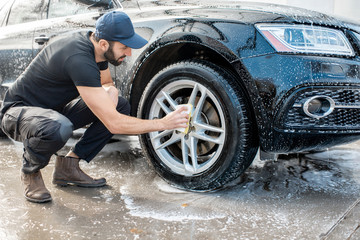Professional washer in black uniform and cap wiping with sponge car wheel during the washing process outdoors