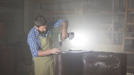 a man in an apron with a beard, is engaged in assembling furniture in a dark authentic workshop