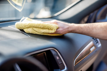 Wiping panel of a luxury car with yellow microfiber, close-up view