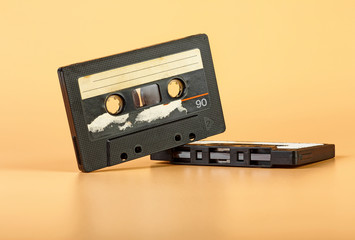 Two vintage audio cassette on brown background