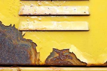 Yellow painted peeled rusted metal door surface detail close up