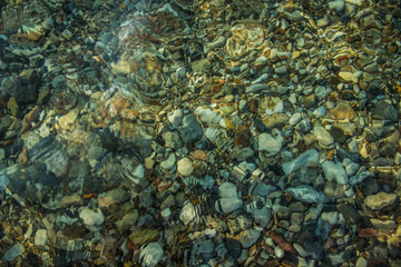 abstract transparent sea water background with view on colorful fuzzy stones bottom, copy space