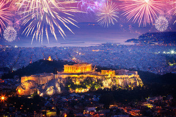 cityscape of Athens with illuminated Acropolis hill and see with fireworks, Pathenon and sea at night with fireworks, Greece