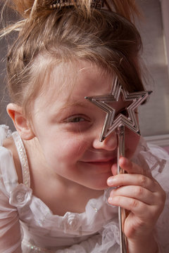Girl looking through star shaped wand