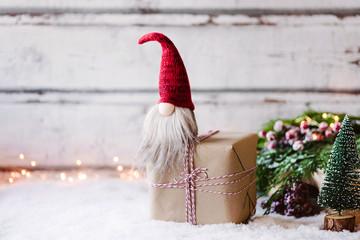 Bald ist Weihnachten! Kleiner Wichtel sitz auf Geschenk  vor weihnachtlich, winterlicher Dekoration