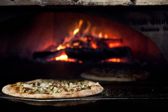 Pizza pies being made in a wood fire oven