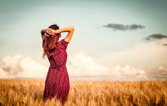 Style redhead girl in red dress tay on yellow wheat field in sunset time and looking forward. Image with cracks and filter