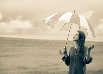 Beautiful adult girl in sweater with umbrella at wheat field and cloudscape on background. Image in...