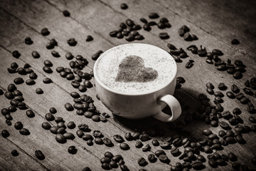 Cup of coffee and heart shape symbol in it on wooden table. Above view. Image in black and white color style.
