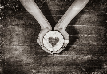 female hands holding a cup of coffee and heart shape symbol in it on wooden table. Above view. Image in black and white color style.