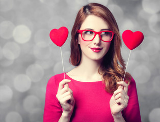 Style redhead adult girl in red glasses and dress with two heart shapes on gray background.