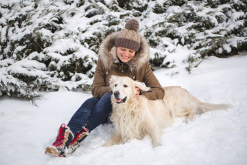 Beautiful girl playing with her dog in the snow. Golden Retriever