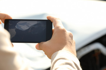 Man photographing broken car after accident for insurance claim, closeup