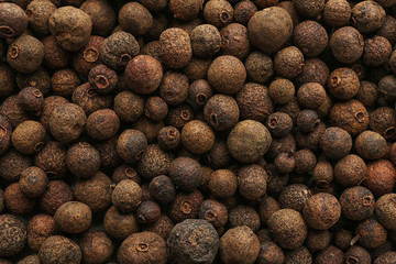 Allspice peppercorns as background, top view. Aromatic spice