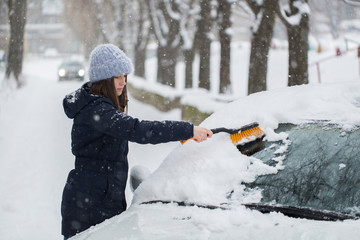 Woman removing snow from car windshield