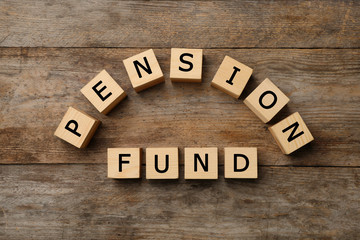 "Cubes with words ""PENSION FUND"" on wooden background"