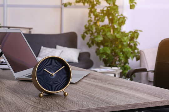 Workplace with stylish analog clock and laptop in office. Space for text