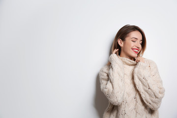 Wall Mural - Beautiful young woman in warm sweater on white background. Space for text