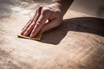 Gritty weathered man's hand and sandpaper; hand sanding a table top to refinish with paint or stain Wall mural