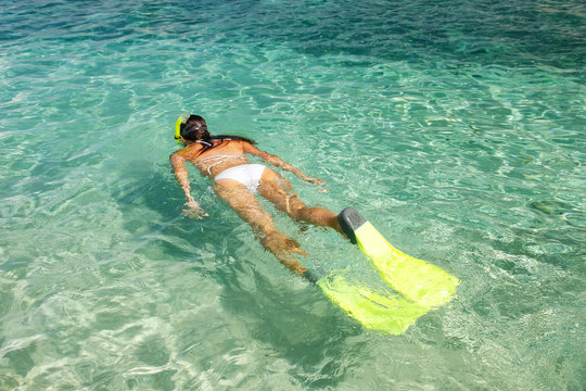 Young woman snorkeling in clear shallow water