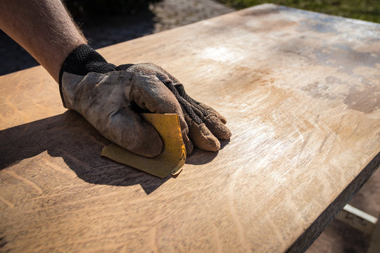 Hand in glove with sandpaper; sanding a table top to refinish with paint or stain
