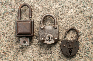 Old weathered grunge retro open and locked padlocks closeup on solid stone surface background