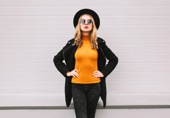 Wall Mural - Stylish young woman model wearing black style clothes, coat, round hat, posing on city street, gray wall background