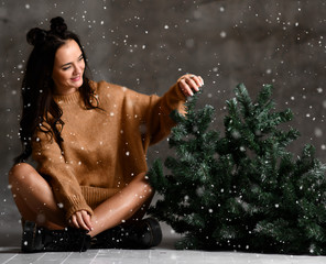 Beautiful hipster woman sitting with Christmas fir tree in sexy knitted sweater blouse under snow